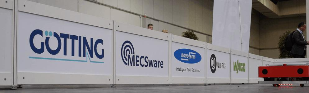 Photo of a KATE AGV in front of the logos of the showcase partners