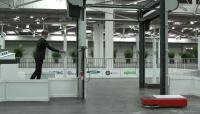 Photo from the showcase showing the automatic doors, a KATE AGV and a person with RFID authentication tag